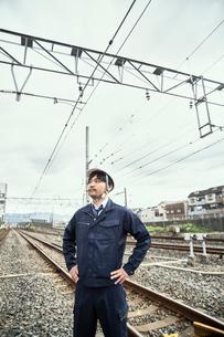 線路をバックに立つ作業服とヘルメットの男性の写真素材 [FYI01464818]