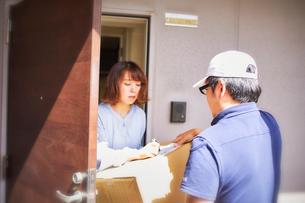 玄関先で段ボールを渡す作業服の男性と受け取る女性の写真素材 [FYI01464822]