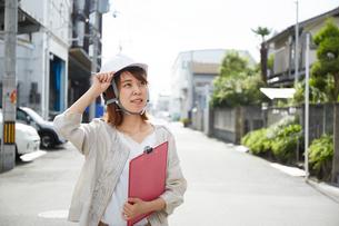 ヘルメットを被り書類を持ちながら道に立つ女性の写真素材 [FYI01464833]