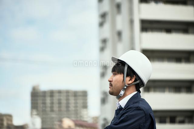 遠くを見ている作業服の男性の写真素材 [FYI01464843]