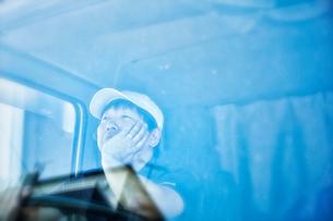 トラックのフロントガラス越しのキャップをかぶった男性の写真素材 [FYI01464846]