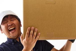 白バックの空間に立つ荷物を肩に持った作業着の男性の写真素材 [FYI01464858]