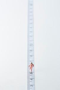 メジャーの上を走るミニチュア人形の女性の写真素材 [FYI01464866]