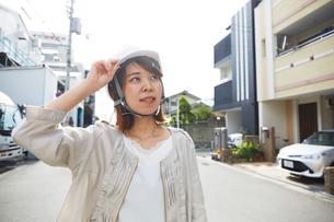 ヘルメットを被り書類を持ちながら道に立つ女性の写真素材 [FYI01464886]