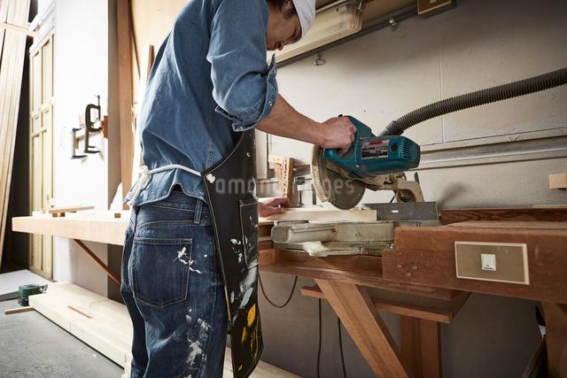 押し切りで木材を切る男性の写真素材 [FYI01464892]