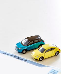 書類と二台のミニカーの写真素材 [FYI01464912]