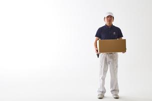白バックの空間に立つ荷物を持った作業着の男性の写真素材 [FYI01464921]