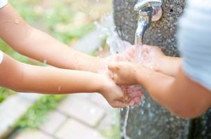 水道の水で遊ぶ子どもの手の写真素材 [FYI01464922]