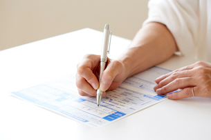 書類に記入する女性の手元の写真素材 [FYI01464941]