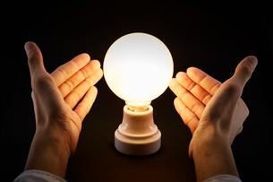 光る電球と男性の手の写真素材 [FYI01464949]