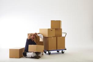 白バックの空間で台車の荷物を落として座り込む作業着の男性の写真素材 [FYI01464953]