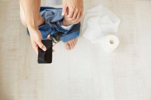 用を足しながら携帯を操作する男性の手元の写真素材 [FYI01464963]