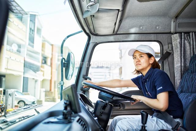 大きなトラックを運転する働く女性の写真素材 [FYI01464964]