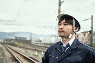 線路をバックに立つ作業服とヘルメットの男性の写真素材 [FYI01464976]