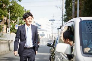 険しい表情の男性と車の窓から顔を出す男性の写真素材 [FYI01464978]