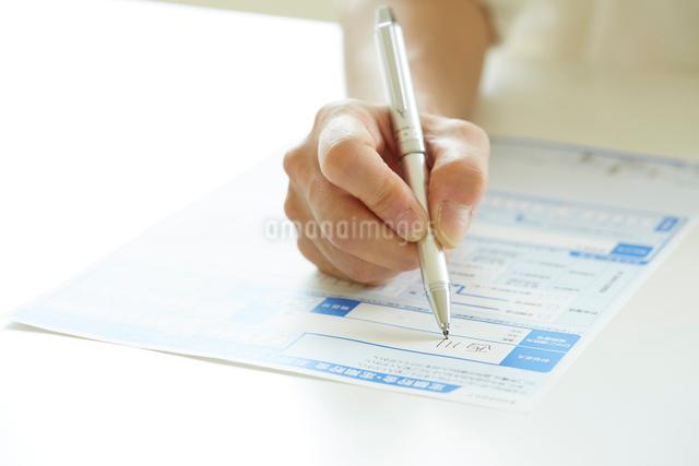 書類に記入する女性の手元の写真素材 [FYI01464983]