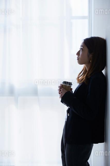 壁にもたれて考え事をする女性の写真素材 [FYI01464988]
