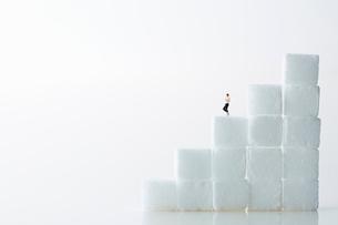 角砂糖の階段を下りているミニチュア人形の男性の写真素材 [FYI01464994]