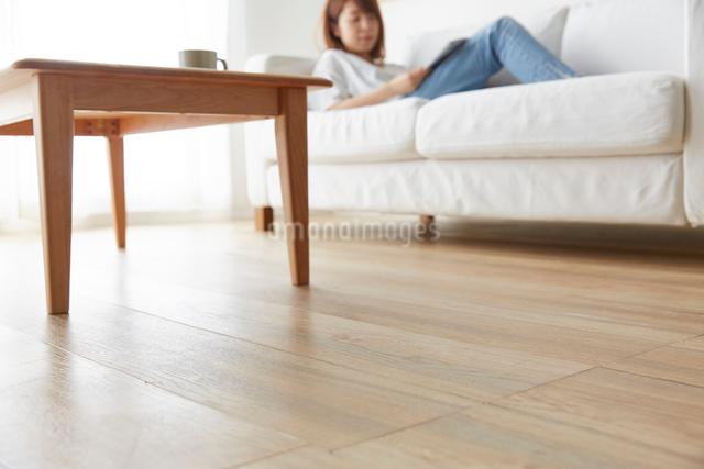 白いソファで雑誌を見てくつろぐ女性の近くの床アップの写真素材 [FYI01465006]