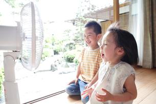 縁側で扇風機にて涼む2人の子供の写真素材 [FYI01465030]