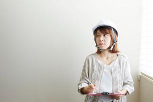 窓辺でヘルメットを被り書類とペンを持つ女性の写真素材 [FYI01465036]