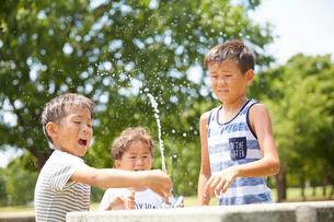 水飲み場で遊ぶ兄弟の写真素材 [FYI01465040]