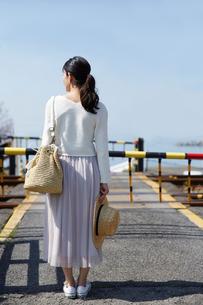 踏切で電車待ちをする女性の写真素材 [FYI01465044]