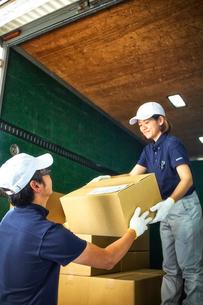 トラックに段ボール箱を積み込む作業服の男女の写真素材 [FYI01465061]