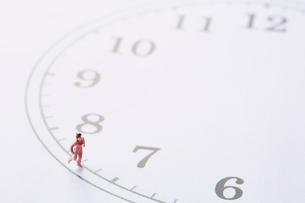 時計の文字盤の周りを走るミニチュア人形の女性の写真素材 [FYI01465062]