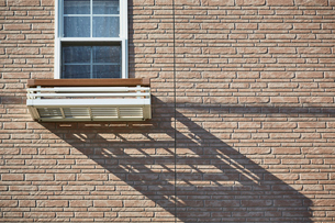 ベージュのレンガ壁の家の小窓の写真素材 [FYI01465063]