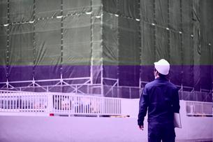 工事中の建物を見ている作業服とヘルメットの男性の写真素材 [FYI01465097]