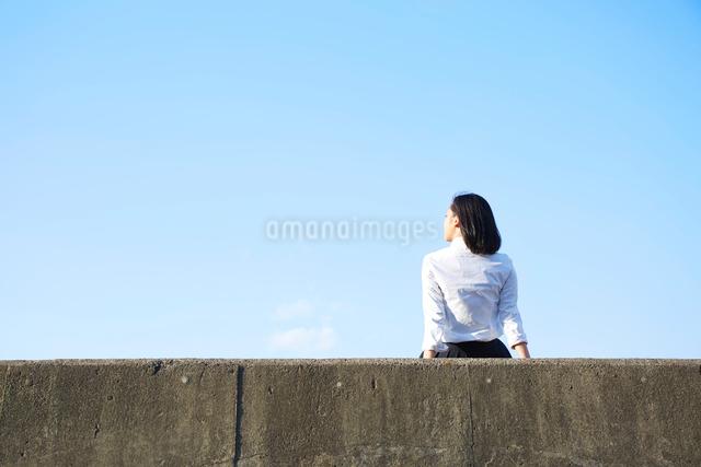 堤防に座る女子高生の後ろ姿の写真素材 [FYI01465104]