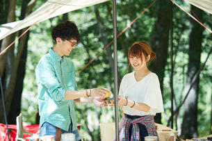 タープの下で一緒に料理をする男女の写真素材 [FYI01465122]