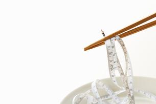 メジャーを掴むお箸のうえに乗るミニチュア人形の男性の写真素材 [FYI01465137]
