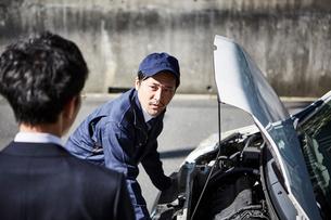 ボンネットを開けて中の様子を見ている作業服の男性と横に立つ男性の写真素材 [FYI01465140]
