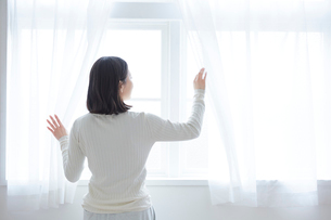 カーテンを開ける女性の写真素材 [FYI01465146]