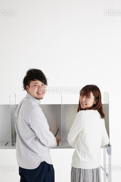 投票記載台の前に立って振り返る男性と女性の写真素材 [FYI01465149]