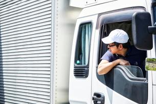 トラックの運転席から顔を出して後ろを確認する男性の写真素材 [FYI01465155]