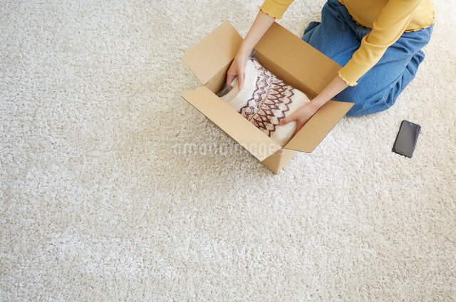 畳んだセーターを箱に詰める女性の手元の写真素材 [FYI01465162]