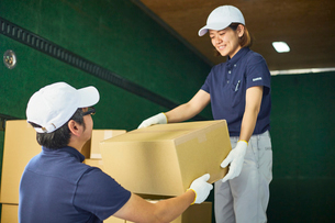 トラックに段ボール箱を積み込む作業服の男女の写真素材 [FYI01465186]
