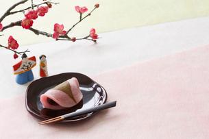 3色の和紙の上の桜餅と梅と雛人形の写真素材 [FYI01465191]