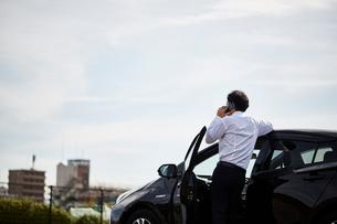 車の横に立ち電話をかける男性の後ろ姿の写真素材 [FYI01465198]