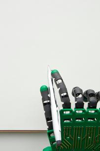紙とペンを持ったロボットの手の写真素材 [FYI01465221]