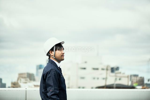 遠くを見ている作業服とヘルメットの男性の写真素材 [FYI01465222]