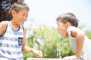 水飲み場で水を飲む男の子の写真素材 [FYI01465239]