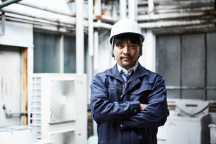 正面を向いて腕組みする作業服とヘルメットの男性の写真素材 [FYI01465249]