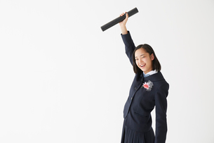 卒業証書の筒を掲げる笑顔の女子高生の写真素材 [FYI01465255]