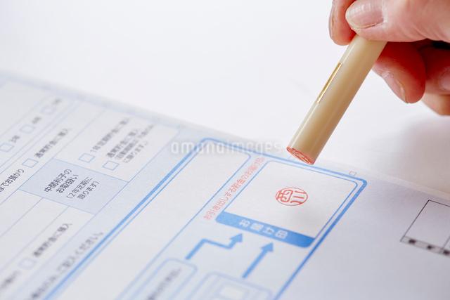 書類と印鑑を持つ女性の手元の写真素材 [FYI01465256]