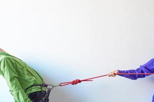 白い壁の前でカラビナがかかったハーネスを引っ張られる登山者の写真素材 [FYI01465257]