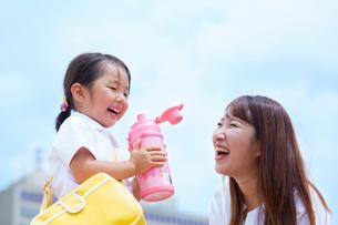 青空を背景に水筒の飲み物を飲む子と見つめる母の写真素材 [FYI01465264]